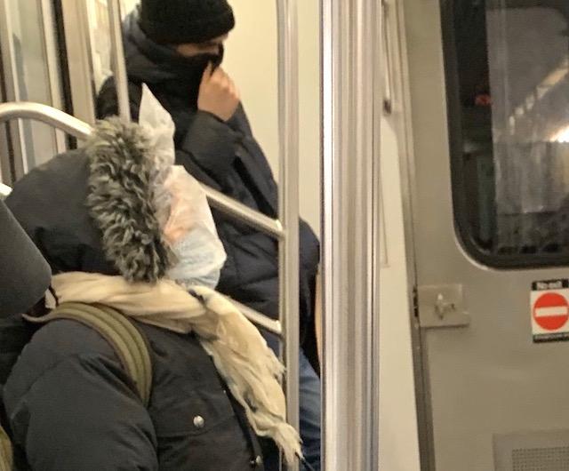 2020年3月18日 地下鉄内での感染を怖れ、ビニール袋で顔を覆う乗客 (C)MM