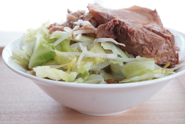 麺に野菜とチューシューをのせているところ